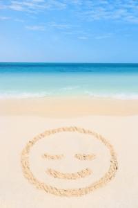 carinha de sorriso na areia da praia