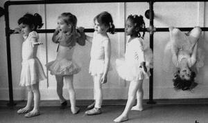 Alunas de ballet na barra e uma delas pendurada de cabeça para baixo