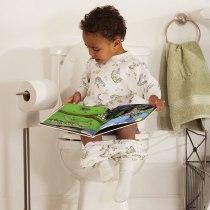 bebê lendo livro sentado no vaso sanitário