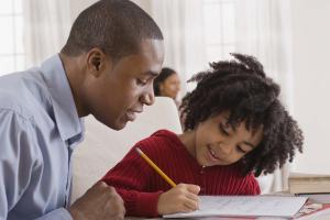 pai observando o filho fazer o dever de casa